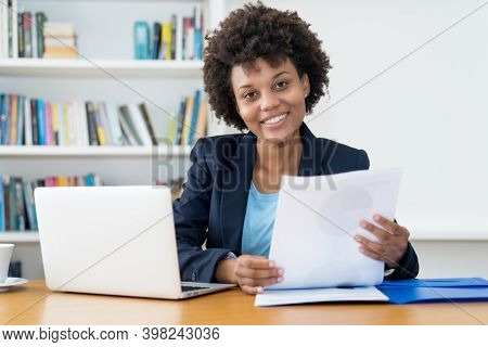 Laughing African American Business Trainee At Work At Desk At Office