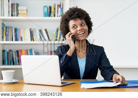 African American Business Trainee Talking With Customer At Phone At Desk At Office