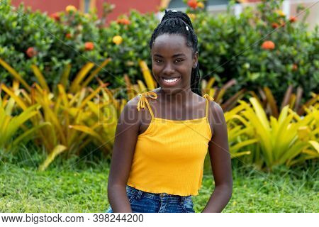 Laughing African American Young Adult Woman With Dreadlocks Outdoor At Park In Summer