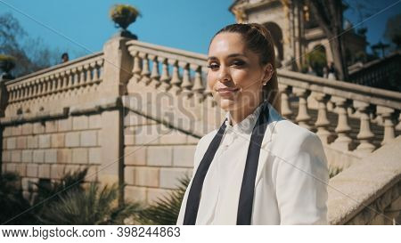Portrait Of Young Posh Woman In Classic White Suit Confidently Looking In Camera In Old Park