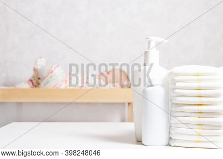 Infant Baby Care Products. Lotion, Powder And Diapers On Changing Table In Nursery. Baby Cosmetics A