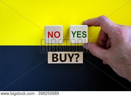 Time To Buy. Businessman Holds A Cubes With Word Yes. Wooden Cubes With Word 'buy'. Beautiful Yellow