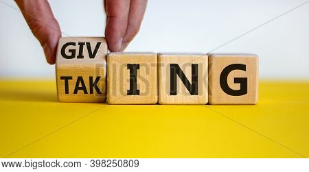 Taking Or Giving Symbol. Hand Turns A Cube And Changes The Word 'taking' To 'giving' On Wooden Cubes