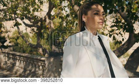 Portrait Of Posh Elegant Woman In White Blazer And Shirt Confidently Walking Through Old Beautiful P
