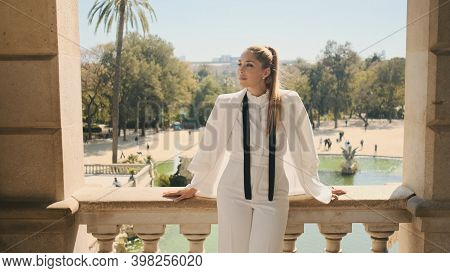 Young Posh Woman In Stylish White Suit Standing On Old Balcony With Beautiful View On Park