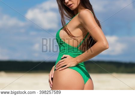 Crop Alluring Female In Green Bathing Suit Standing With Hand On Waist Showing Curvy Body In Sunligh