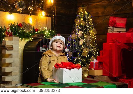 Christmas Kid Wants To Know What Is Inside The Christmas Gift Box. Happy Little Smiling Boy With Chr