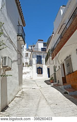 View Of The Narrow Cobble Stone Street In The Old Picturesque Town Of Ojen In Andalusia, Spain