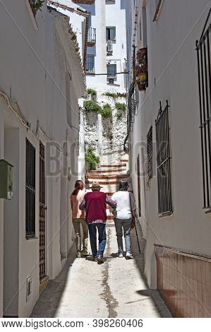 Ojen, Spain - May, 2017: Senior Citizen Is Walking Down A Street With Help Of His Friends.