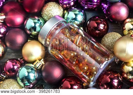 Plastic Bottle With Orange Pills. Curcumine And Vitamin D Capsules On Colourful Christmas Balls. Cor