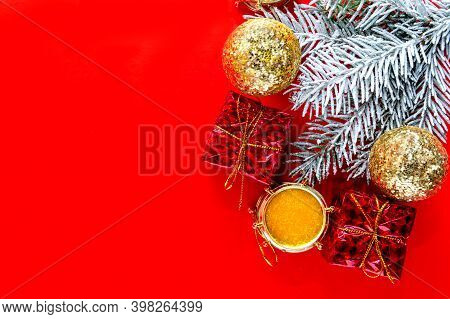 An Arrangement Of Christmas Frame With Fir Branches And A Gift Box. Red Christmas Background. Copy S