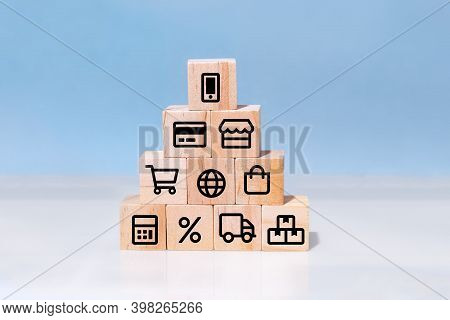 Online Shopping Or E-commerce Concept With Online Business Icons On Wooden Cubes Against Blue Backgr