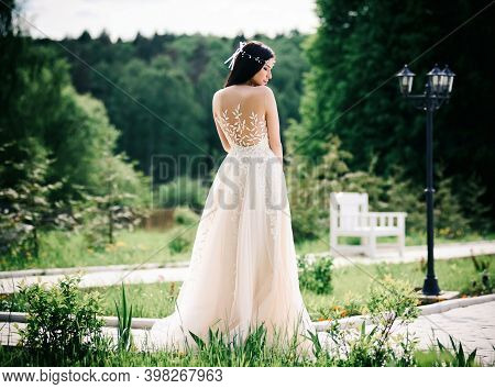 A Bride In A Wedding Dress With An Open Back On A Summer Natural Background. Young Brunette In A Whi