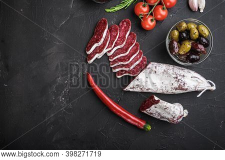 Spanish Longaniza Salami Sausage Slices With Herbs On Balck Background, Top View With Copy Space