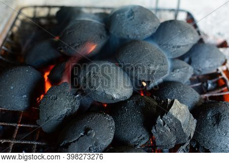 Pile Of Round Briquettes Of Charcoal On Grill, The Fire Just Lit, Preparation For  Barbeque Has Just