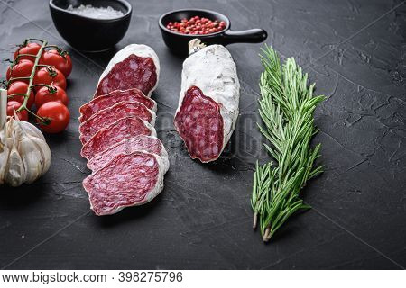Dry Cured Salchichon Sausage Slices With Herbs On Balck Background