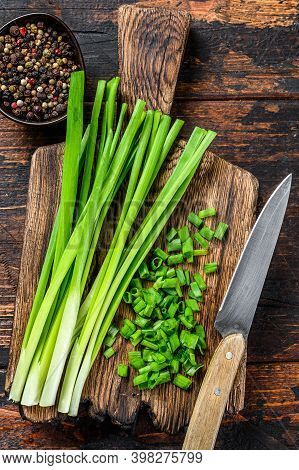 Cut Green Onions Chives On A Cutting Board. Dark Wooden Background. Top View