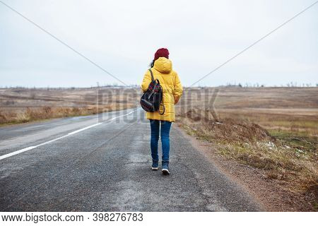Backview Of A Female Tourist With A Backpack Wearing Yellow Jacket And Red Hat Walks On The Road. Yo