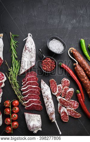 Set Of Various Spanish Dry Cured Salami Sausages Slices And Whole Cuts On Balck Background, Flat Lay