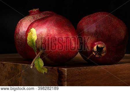 Two Entire (whole) Pomegranate Fruits Against Dark Background - Still Life Concept