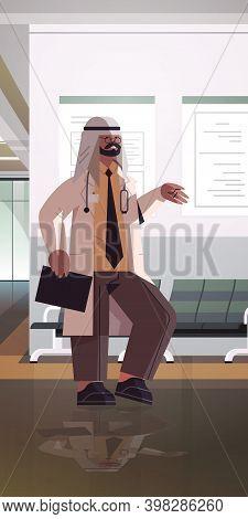 Muslim Man Doctor In Uniform Arabic Male Medical Professional Standing In Hospital Corridor Medicine