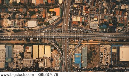 Top down of traffic roads at Manila town cityscape aerial view. Amazing urban scenery with cars and buses on roadway. Downtown skyscrapers, buildings roofs of Philippines capital city