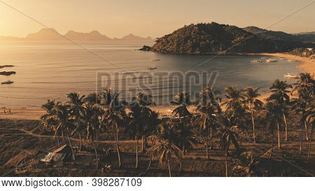 Sun seascape at tropic island aerial. Grass sea shore with palm trees. Sand beach at ocean coast with ships, vessels. Summer tropical nobody nature landscape El Nido Island, Palawan, Philippines, Asia