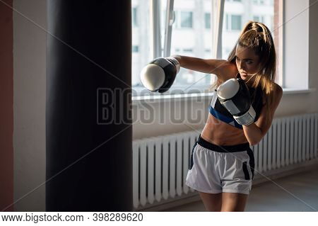 The Girl Is Preparing For A Boxing Competition And Trains Punches On A Punching Bag In A Spacious Gy