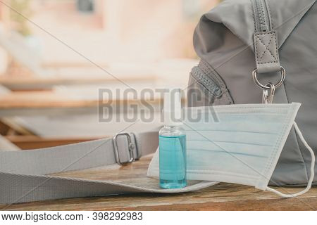 Blue Alcohol Spray Bottle And Medical Face Mask With Lady's Shoulder Bag On Wooden Desk , New Normal