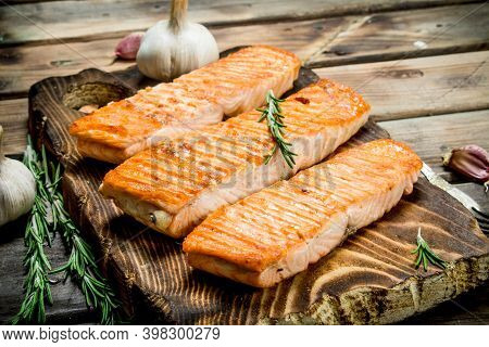 Grilled Salmon Fillet With Garlic And Rosemary. On A Wooden Background.