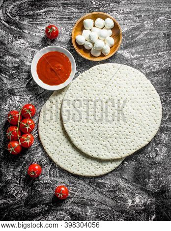 Raw Pizza. Rolled Out Dough With Tomato Paste, Tomatoes And Cheese. On Rustic Background