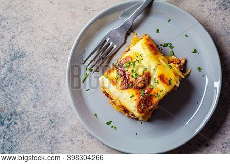 Traditional Greek Potato And Meat Casserole With Cheese - Moussaka, Dark Background. Greek Cuisine C