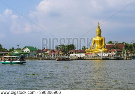 View Of The Large Golden Buddha Statue And The Boat By The Chao Phraya River In Nonthaburi Province