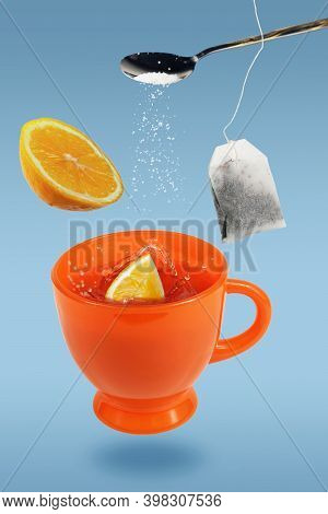 Levitating Orange Teacup With Spoon, Tea Bag And Lemon Over The Blue Surface