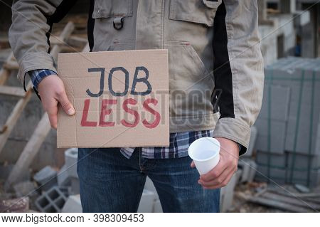 Construction Worker Stands With Placard Jobless Opposite Construction Site