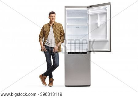 Full length portrait of a casual male teenager in checkered shirt and jeans leaning on an empty fridge isolated on white background