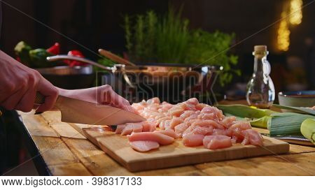 Woman slicing meat for cooking on kitchen table. Closeup hands. Cosy dark room. Real, authentic cooking.