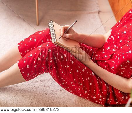 Crop Woman Sitting On Floor At Home In Solitude Writing Her Dreams Or Letter For Santa Claus With He