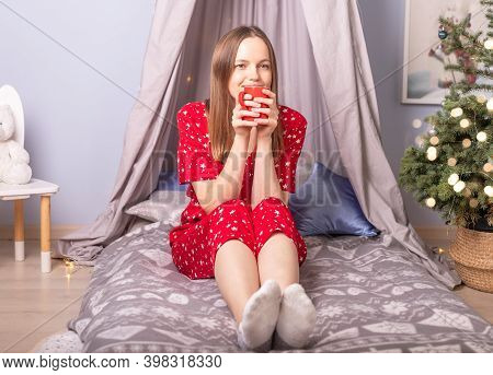 Alone Young Woman On Bed Drinking Tea And Dreaming In Red Pyjamas In Decorated Room At Christmas Tim