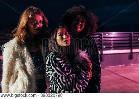 Thee Stylish Girls Looking At Camera At Night