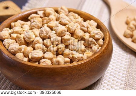 Chickpeas In A Wooden Bowl On Kitchen Table. Raw Chickpeas Close-up