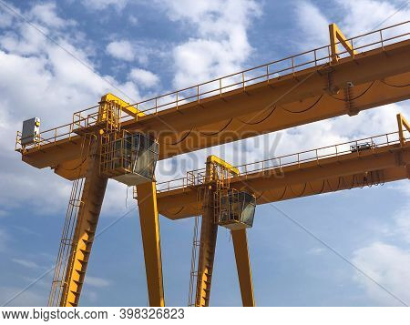 Gantry Cranes Opposite Cloudy Sky. Industrial Lifting Machinery. Hoist, Winch