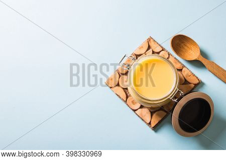 Ghee Or Clarified Butter In Jar And Wooden Spoon On Blue Background. Top View. Copyspace. Ghee Butte
