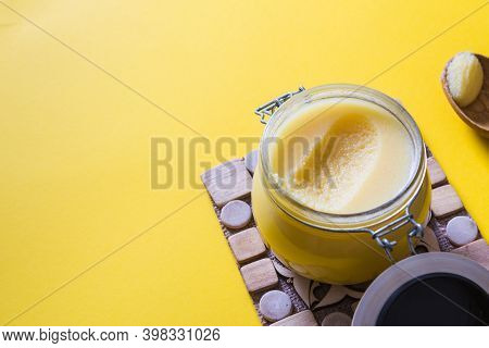 Ghee Or Clarified Butter In Jar And Wooden Spoon On Yellow Background. Top View. Copyspace. Ghee But