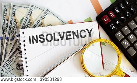 Word Text Insolvency. Business Concept With Chart, Dollars And Office Tools