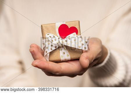 Beauty Woman Hands Holding Gift Box With Red Heart And Heart On Light Background, Close-up. Pastel C