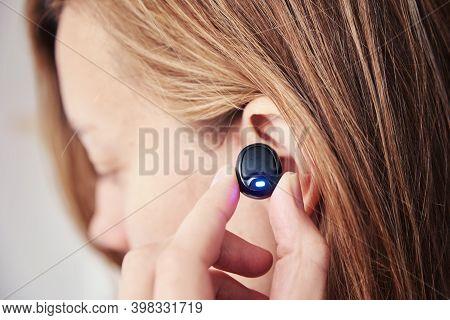 Woman Listening Music Through Wireless Earphones. Caucasian Woman Using Bluetooth Headhones In The E