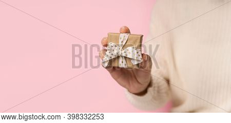 Beauty Woman Hands Holding Gift Box With Heart Ribbon On Pink Background, Close-up. Pastel Colors, C