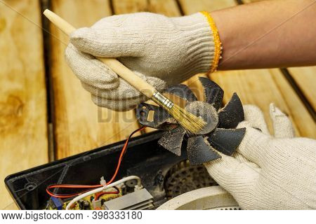 Master Cleans The Fan Of The Electric Stove On A Wooden Background. Hands In White Gloves Hold A Bru