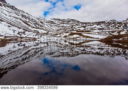 Cloudy sky reflected in the smooth water of an alpine lake. The first snow fell on Grossglockner Alpine Road. Austria. Ecological, active and photo tourism concept